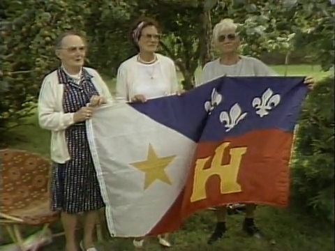 Three women holding acadian flag